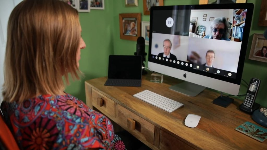 Woman watching virtual event on computer